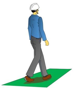 Worker walking on the green belt