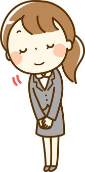 お辞儀をするスーツの女性