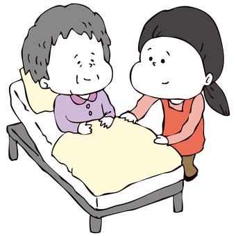 ベッド介助をする介護士女