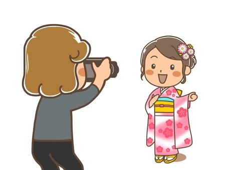 A woman in a kimono is taking a commemorative photo