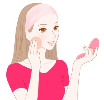ファンデーションを塗る女性ピンク