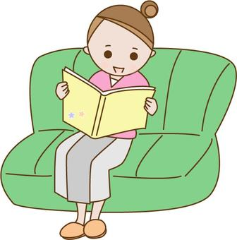 A woman sitting on a sofa and watching a magazine