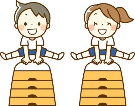 跳び箱を飛ぶ女の子と男の子