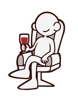 椅子に座ってワインを飲む人