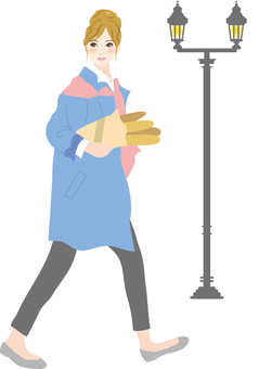 A woman walking around the city with a bucket
