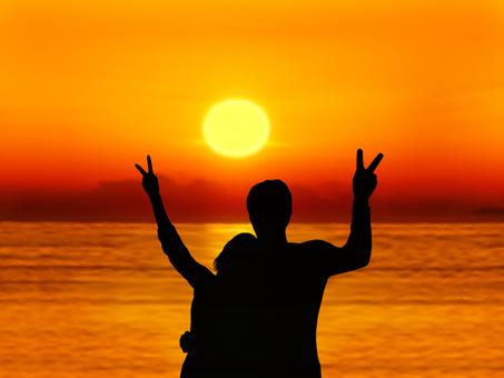 Peace sign toward the setting sun