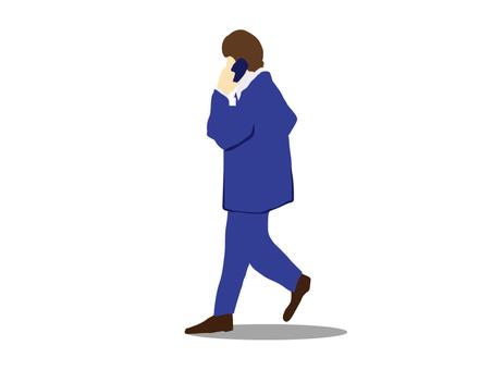 Businessman walking while talking on mobile