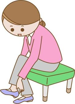 A woman sitting in a chair and putting on her shoes