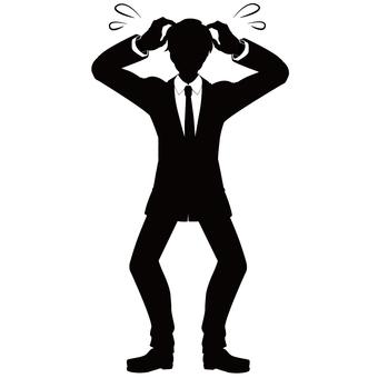 頭を抱える スーツ姿の男性シルエット