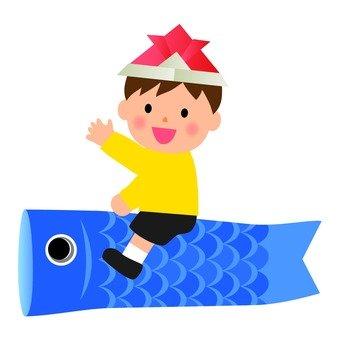 A boy riding a carp streamer