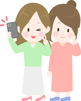 Illustration of two women taking a picture with a smartphone