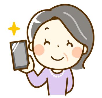 拿著有微笑的資深婦女一個智能手機