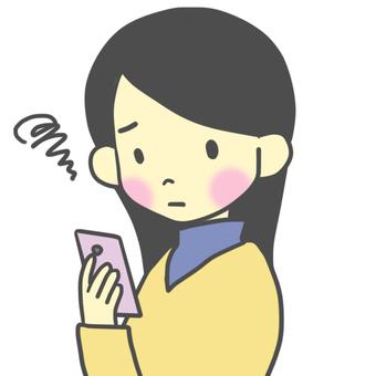 一位女士不安地望著智能手機