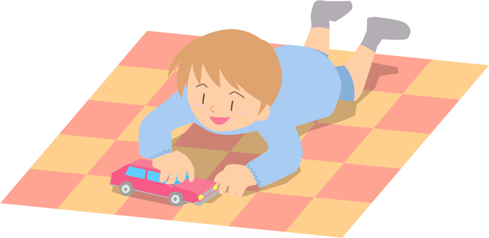 Kindergarten child playing with a toy car lying on the floor