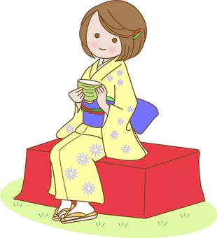 A woman in kimono drinking tea