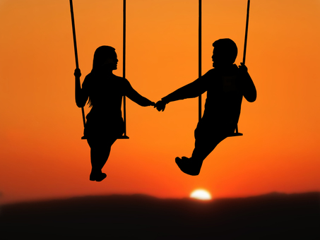A couple with a sunset and a swing