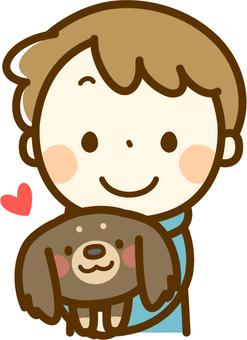 A boy holding a dachshund
