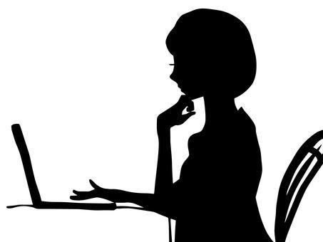 一個女人使用個人電腦(剪影)