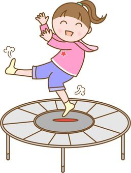 A girl playing with a trampoline