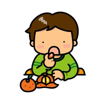 みかんを食べる男の子