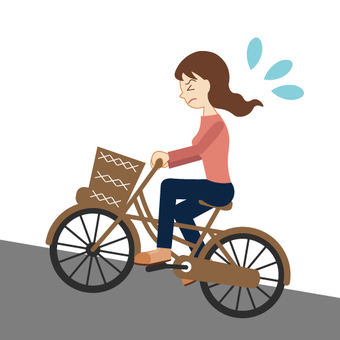 A woman riding a slope by bicycle