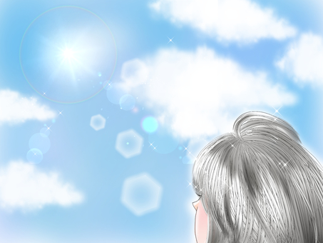 A woman looking up at the blue sky